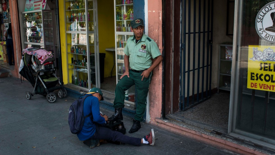 A private security guards gets his boots shined as he stands guard to a shop in downtown Guatemala City. Deteriorating security has created a boom for private security firms. According to one estimate, private security guards outnumber police officers in the country by almost four to one.