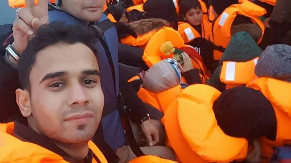 Afghan student journalist Omid Ahmadi and fellow refugees in a rubber dinghy on the sea crossing from Turkey to Greece.