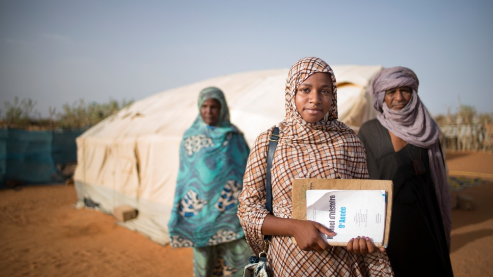 Malian refugee Tinalbarka, 16, with her parents as she leaves the family tent to attend classes at secondary school in Mbera refugee camp in Mauritania.