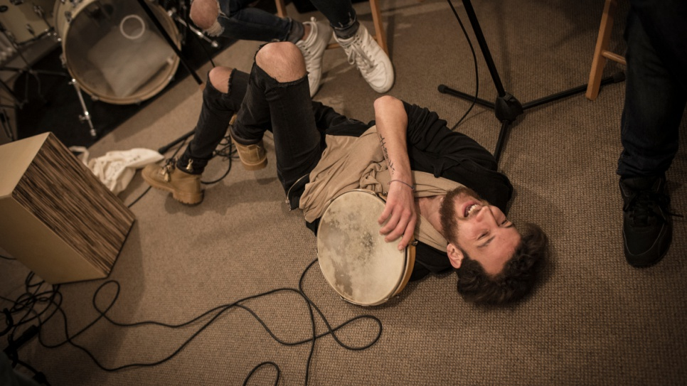 Syrian drummer Ali Hasan lies on the floor laughing during Musiqana's band practice at the Super Sessions cafe in Berlin.