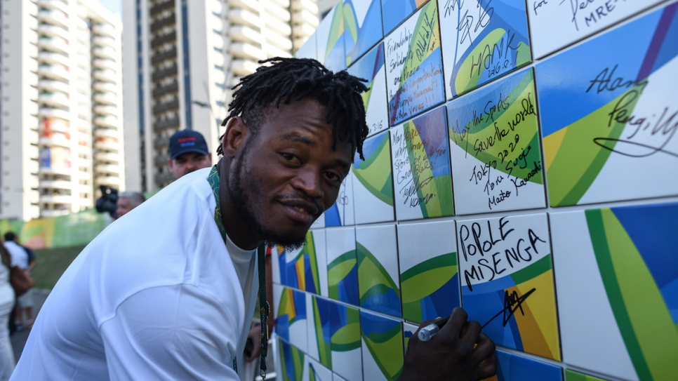 Popole Misenga from Congo signs the Olympic Truce Wall in Rio's Olympic Village.
