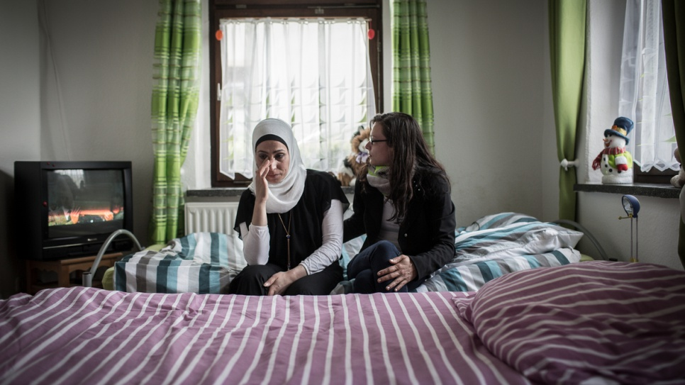 Layali Radwan is comforted by her landlord, Anna Polonko, in her small apartment in the German town of Thalheim.