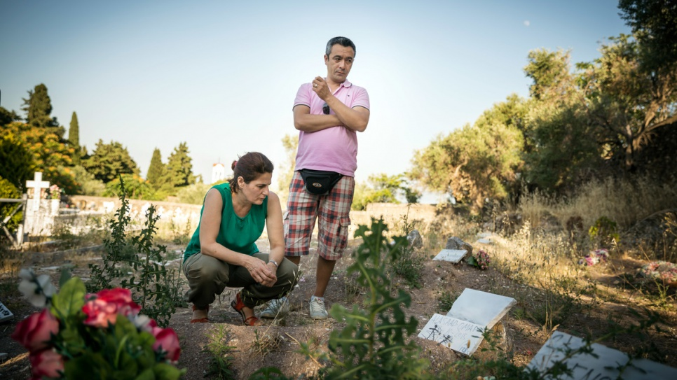 Efi Latsoudi, along with friend and interpreter Mohammadi, takes a moment to reflect at a cemetery where many refugees who drowned in the Aegean Sea now lie.