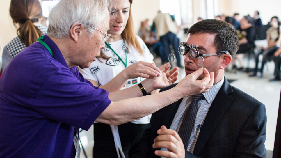 Optometrist Akio Kanai examines Yalchin Aghayev's eyes at a temporary clinic in Barda, Azerbaijan. Aghayev, who was displaced from his home by war two decades ago, was five years old when an accident left him with poor vision.