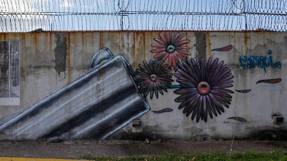 A mural in San Pedro Sula shows flowers emerging from a gun barrel. In 2014, the gang-ravaged city had the highest murder rate in the world.