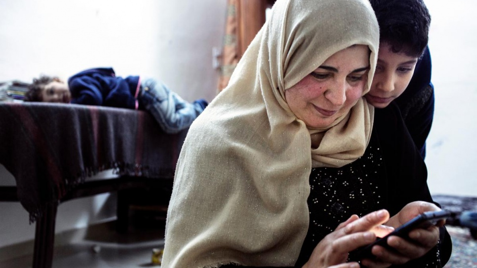 Syrian refugee Bushra sits with her children in Jordan in 2015, showing them images and text messages from their father, who left months earlier for Europe.