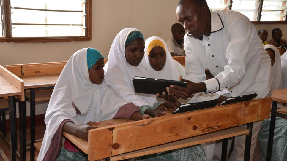 Michael Mutinda, a teacher in one of the primary schools at Dadaab refugee camp in Kenya, shows his pupils how a tablet computer works, in this 2014 file photo.