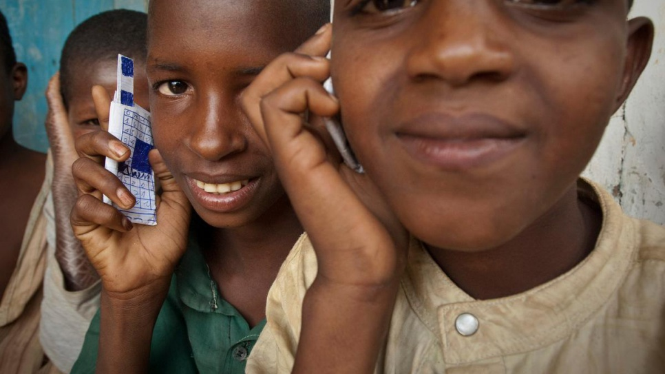 Children at a school in Gbiti, Cameroon, play with cellular phones that they drew, in this 2009 file photo.