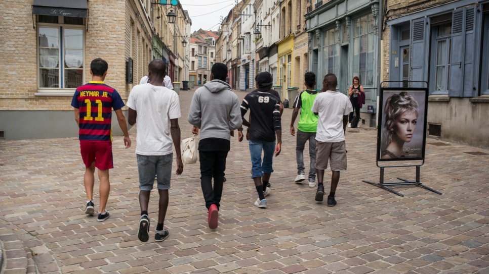 A group of unaccompanied children from Afghanistan, Chad and Sudan walk through the streets of Saint-Omer on their way to a gardening lesson.