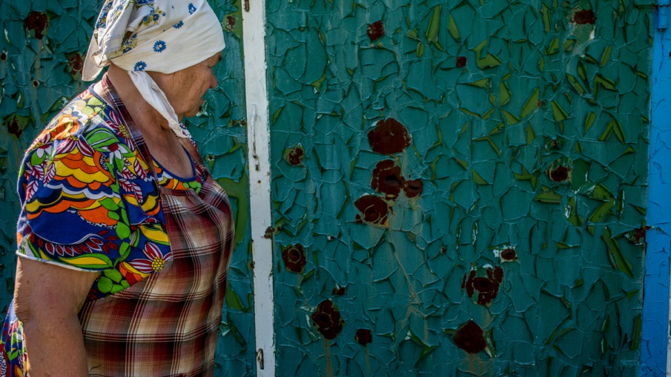 Shrapnel holes in an iron gate remind Ekaterina Belyavtseva of the conflict which raged near her home in eastern Ukraine during 2014.