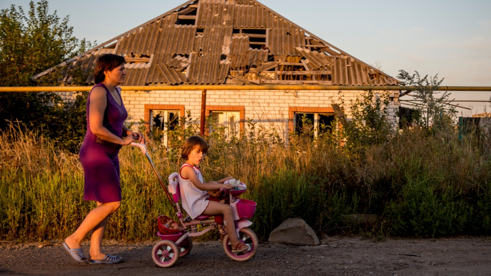 A mother and daughter stroll past a house partially destroyed in the 2014 conflict in eastern Ukraine.