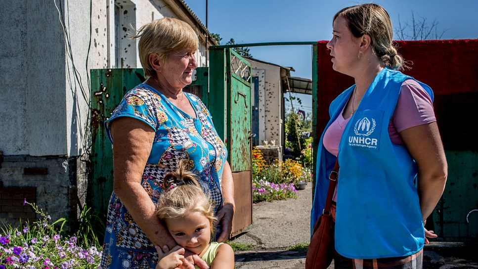 A UNHCR staff member talks to a local resident whose home was ruined in the 2014 fighting in the Luhansk region of eastern Ukraine.