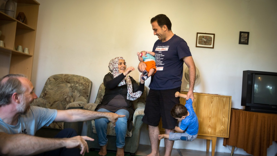 Fatima and her husband Moufid play with their children in their new home in Röhrsdorf, Germany.