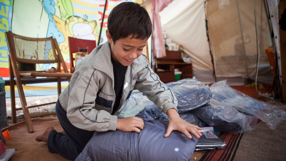 An Afghan boy opens a winter kit that will help him face harsh weather conditions at the open accommodation site of Agios Andreas in Attica, Greece.