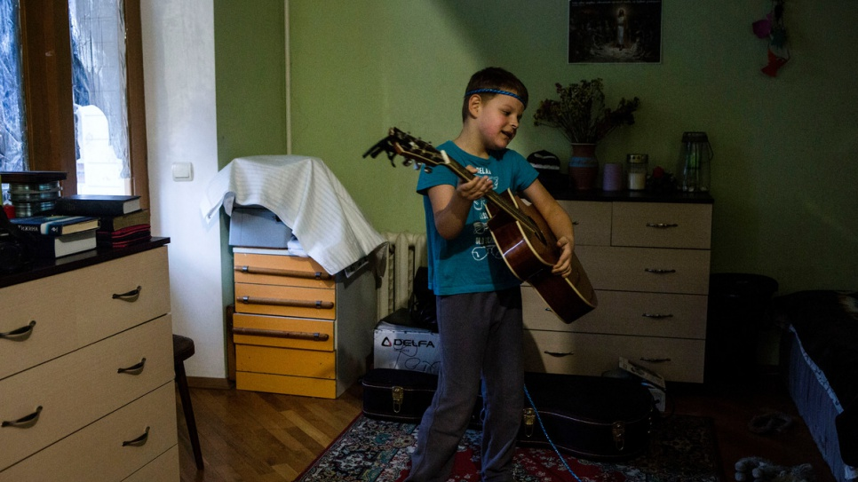 Igor pretends to play his father's guitar while at home in Kiev.