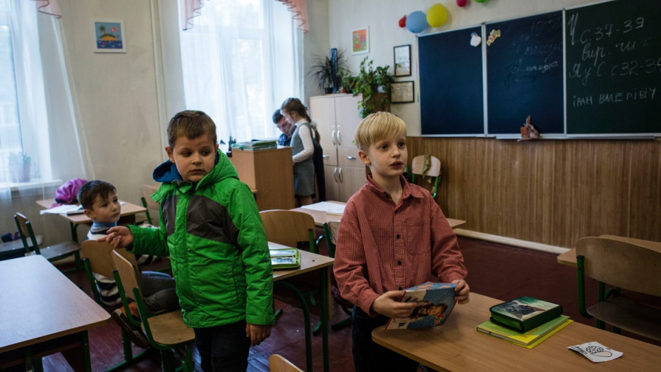 Igor (L) arrives at school with his mother to pick up Ivan (R).