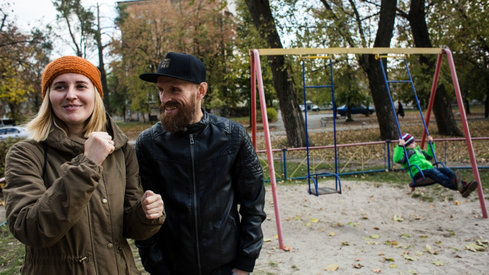 Anna and Gesha sing together as their youngest son, Igor, plays on the swing at a playground near their apartment.