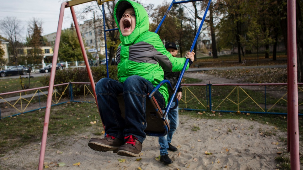 Igor roars with delight on the swing as his father, Gesha, looks on.