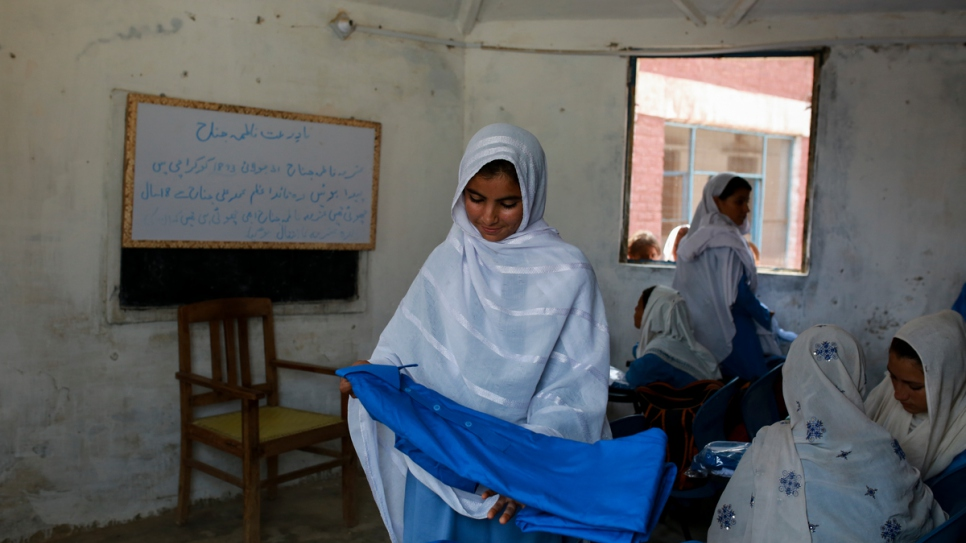 A young student admires her new uniform at Aqeela's school in Kot Chandana.