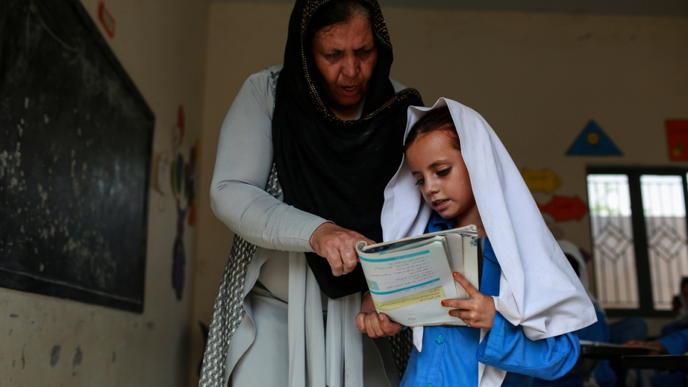 Aqeela Asifi helps one of her young students. The 2015 Nansen Award winner started this school in 1992 with a borrowed tent and handwritten texts.