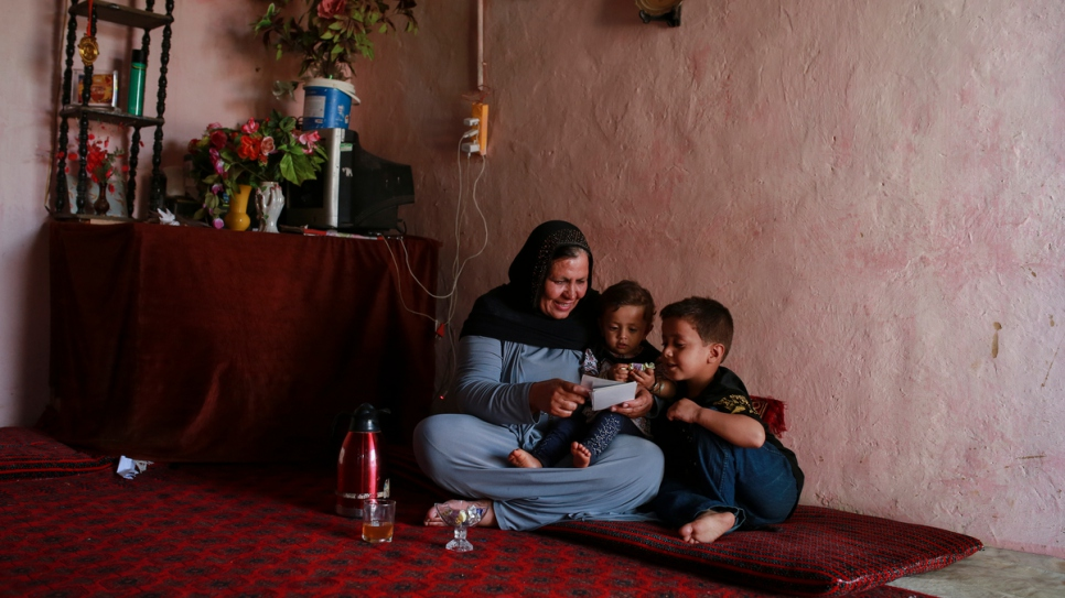 Aqeela shows photos of her younger days in Afghanistan to her grandchildren at her house in Kot Chandana refugee village.