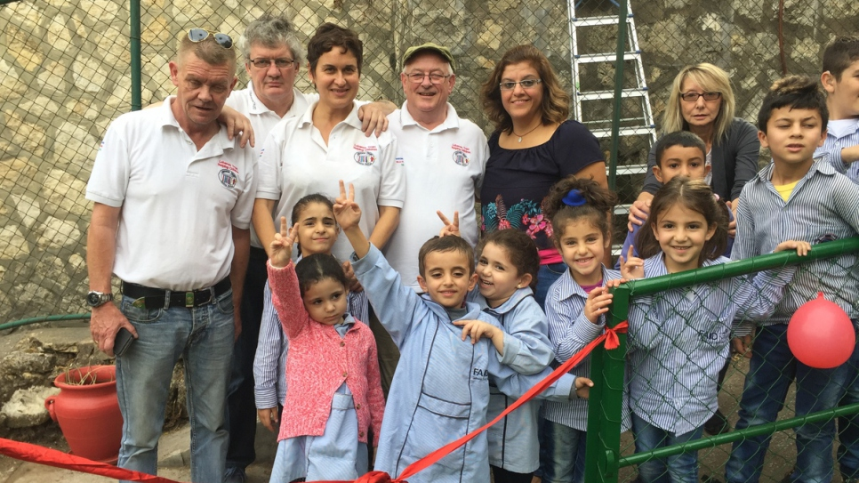 Christy Kinsella (hat), chairman of the Lebanon Trust with others on the playground of FAID.