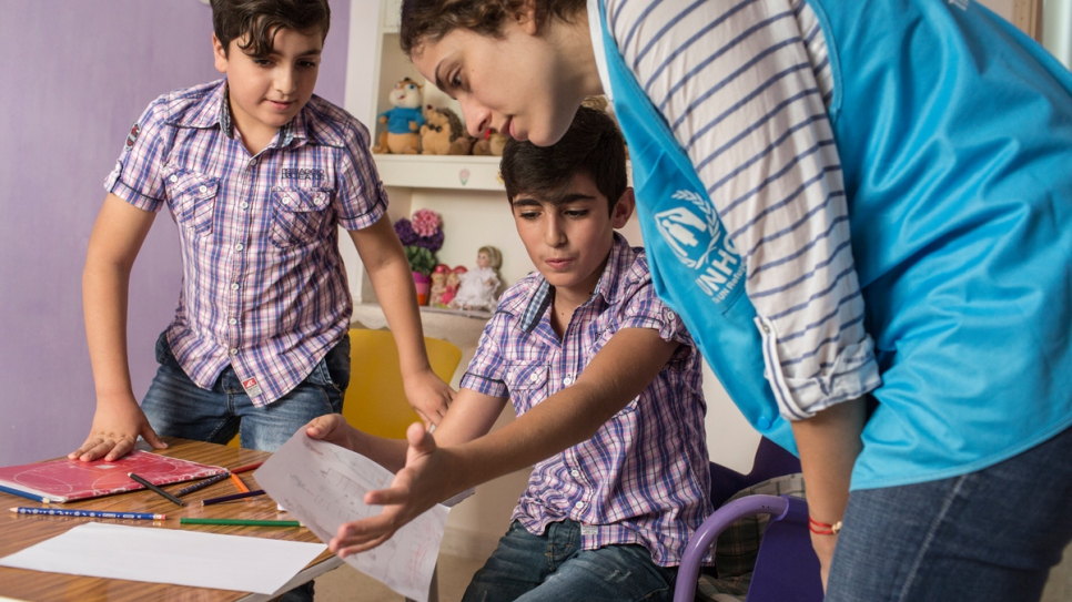 Adib* (L) and his brother Bushra*, 10, from Aleppo, show their drawings to UNHCR staff member Dana Sleiman, in their home in Lebanon.