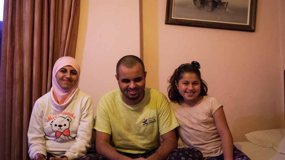 Ashraf, who is blind, sits with his sisters Ghufran and Salam inside the room they share at the Rovies Hotel.