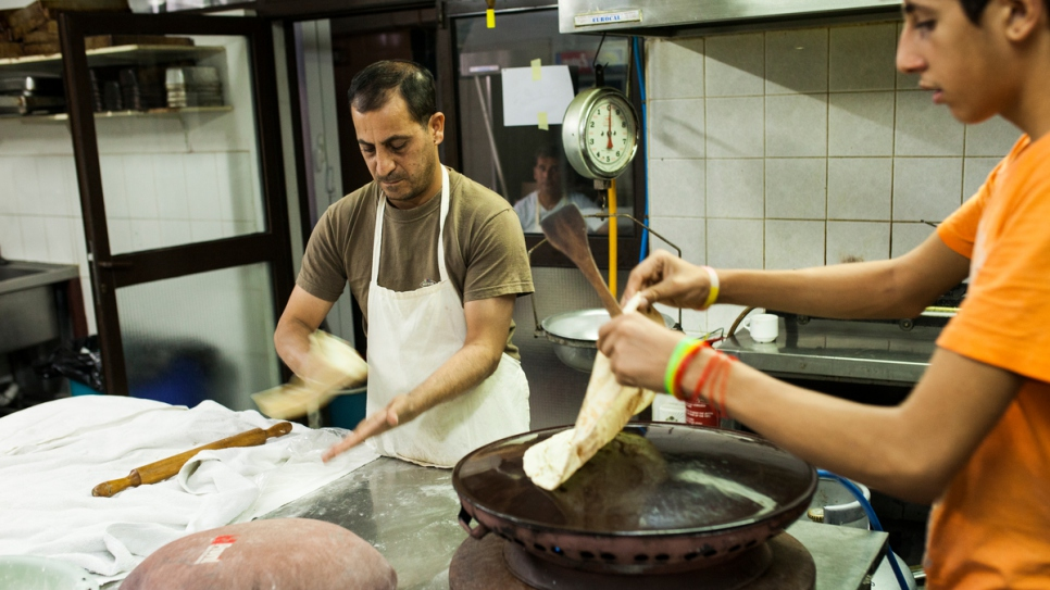 Syrian refugees prepare traditional bread in the kitchen of the Rovies Hotel.