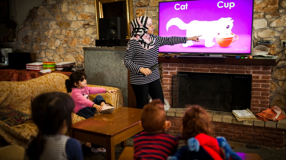Manar, a Syrian refugee who fled home with her three children, teaches English to a group of young children.