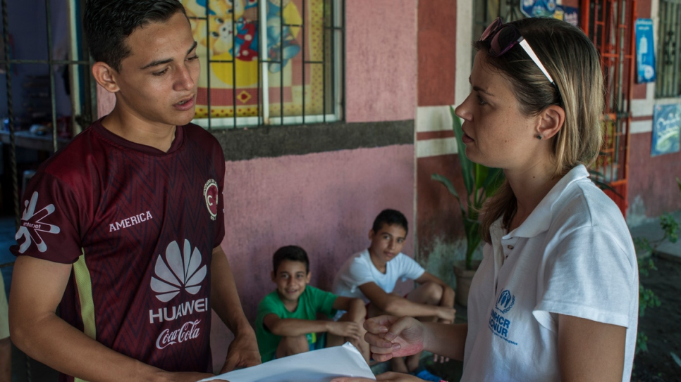 A UNHCR protection officer talks to Moises, Anderson and Jairo.