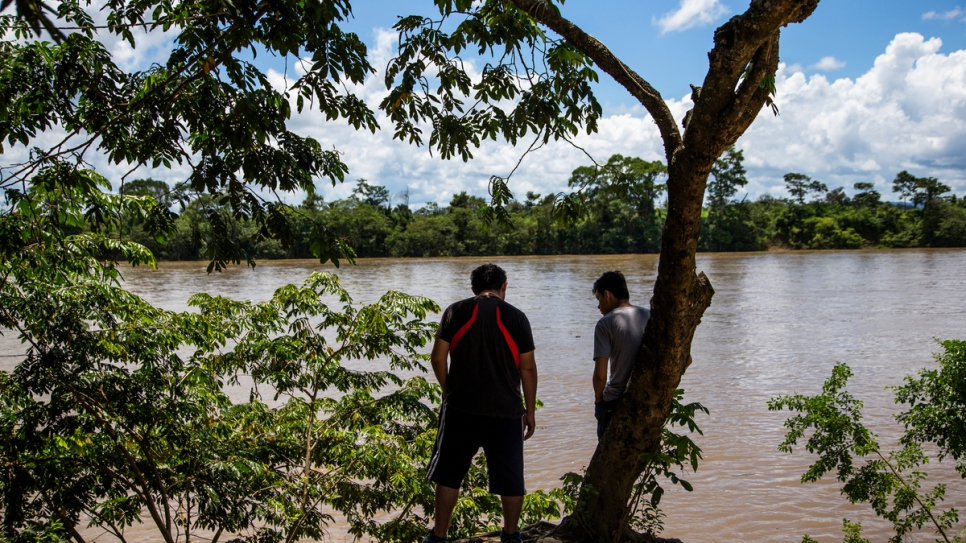 Two young Honduran men wait on the banks of the Usumacinta River in La Técnica, Guatemala. They will be charged 150 quetzales (about US$20) to cross by boat to Mexico on the far side.