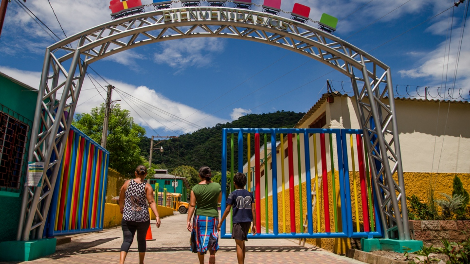 A family enters the gates of a government-run day centre in Santa Ana, El Salvador, that gives workshops and skills training to adolescents and provides a safe space away from gang life.
