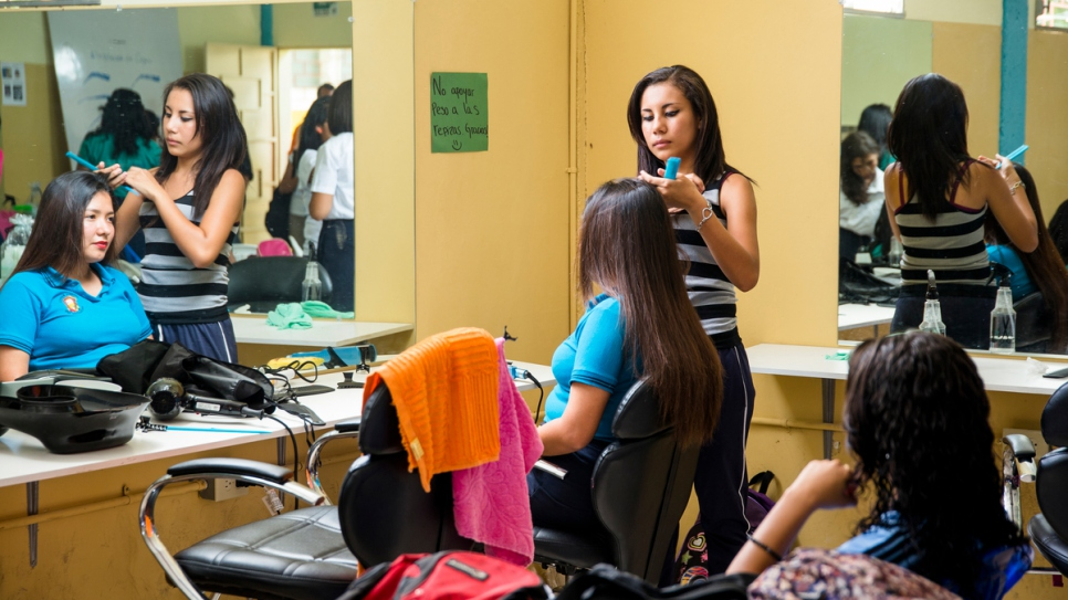 A young girl practices her hair straightening skills at a beauty salon workshop at a government youth and community centre in Santa Ana, El Salvador.