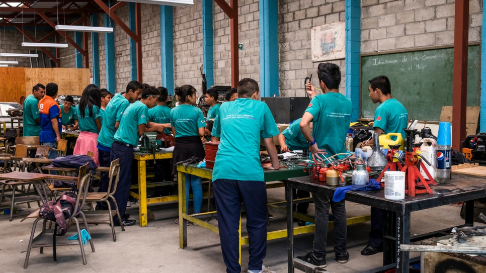 A group of youngsters learn how to repair an engine at a car mechanics workshop at a government run youth and community centre in Santa Ana, El Salvador.