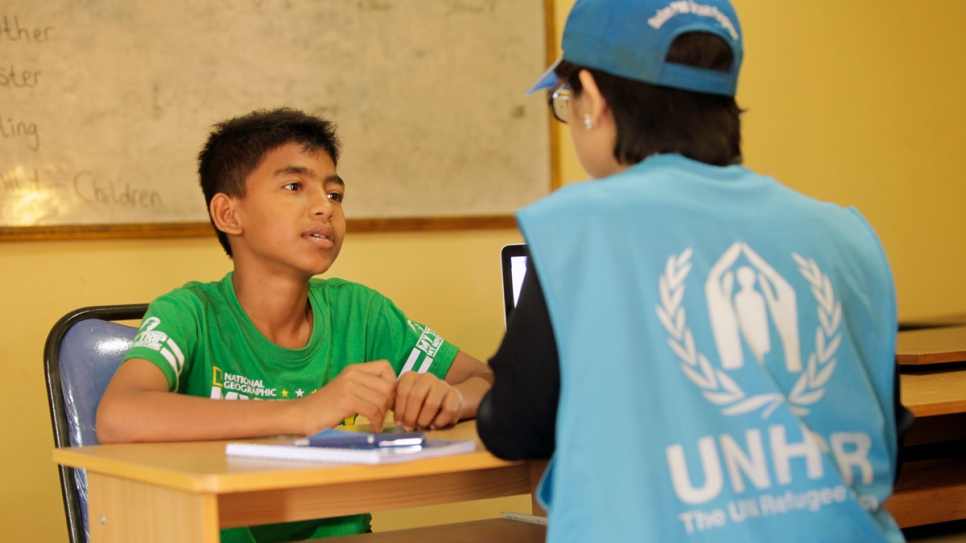 Yasin, a 10-year-old Rohingya refugee, speaks with a UNHCR staff member in Indonesia.