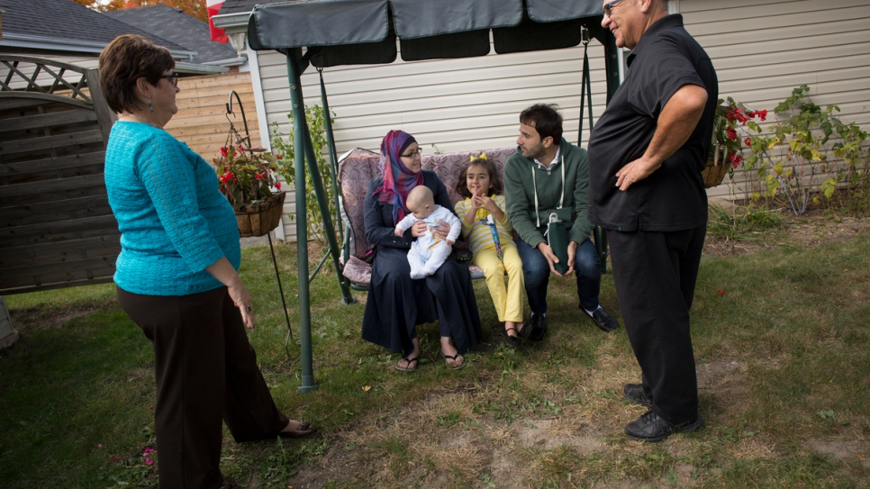 Volunteers Tanna and Joe sit with Husam, Noura, Bayan and six-month-old Adam in the back garden of their house in Peterborough.