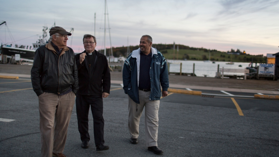 David Friendly (left) and Father Michael Mitchell spend time with Ahmad Ayash on the pier in Lunenburg.