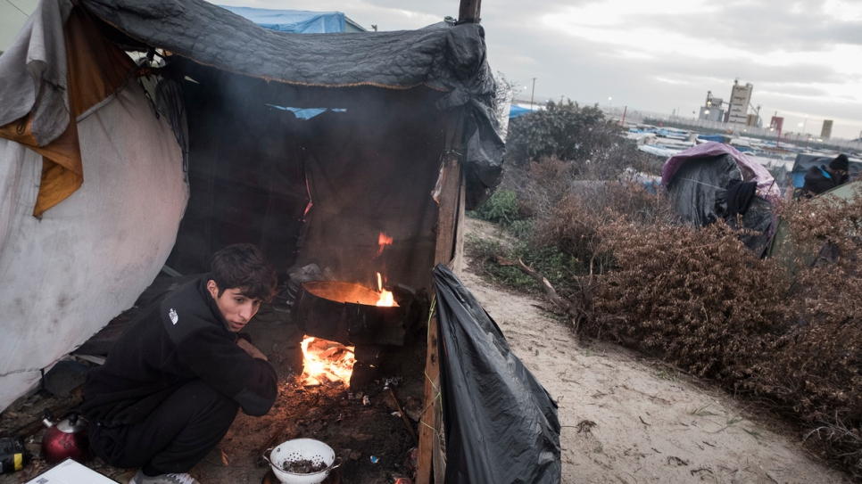 A young Afghan refugee prepares dinner in a makeshift kitchen in Calais, France, October 12, 2016.