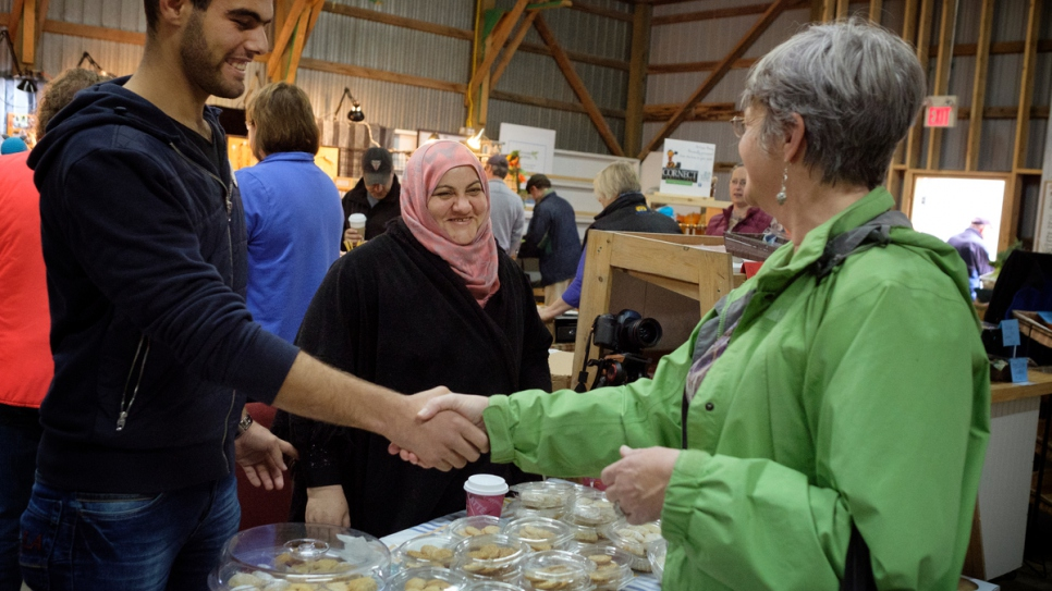Rabiaa and her son, Majd, greet a customer at the weekend farmer's market.