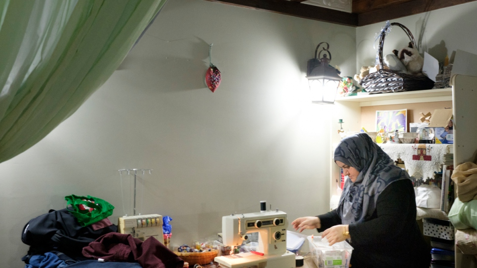 Rabiaa uses a sewing machine to adjust an item of clothing for a client.