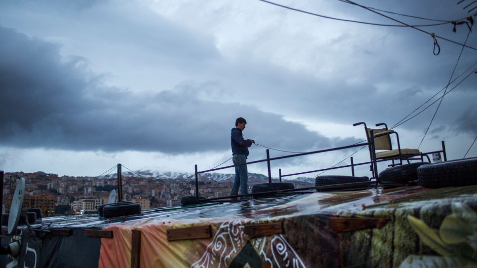 A young Syrian refugee tries to fix the wiring on top of a shelter at an informal settlement in the Bekaa Valley, Lebanon.