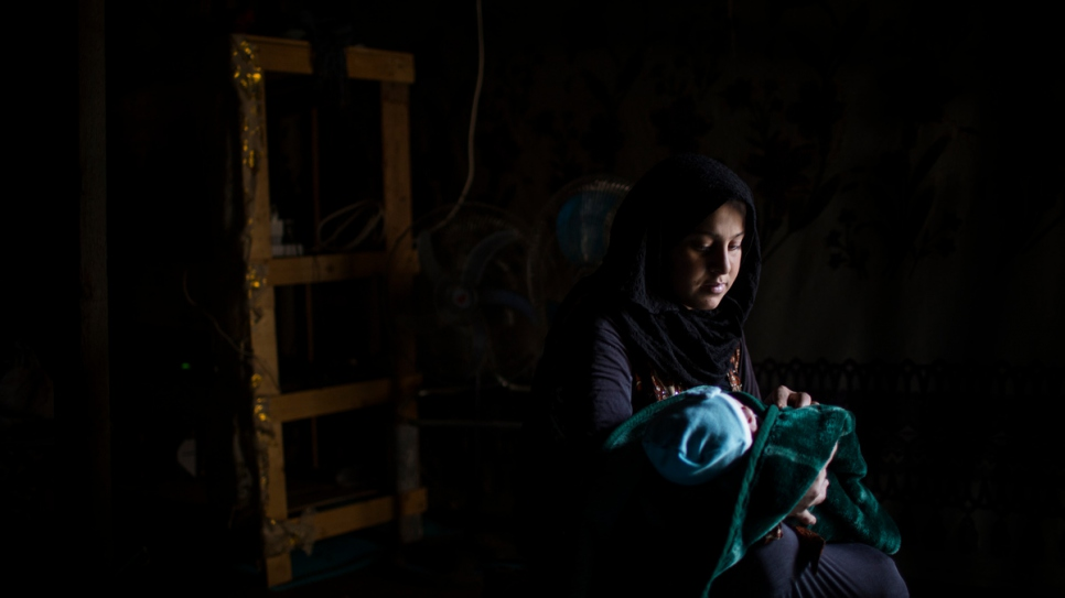 Syrian refugee Muna, 19, holds her newborn son Mahmood, at her temporary shelter in the informal settlement of Tal Sarhoun, Bekaa Valley, Lebanon.