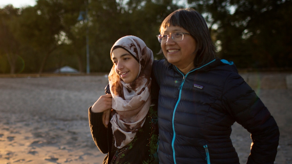 Thuy Nguyen and Narjes Nouman spend time at a beach in downtown Toronto. Nguyen arrived as a refugee more than 40 years ago and now serves as a mentor to newly arrived Narjes.