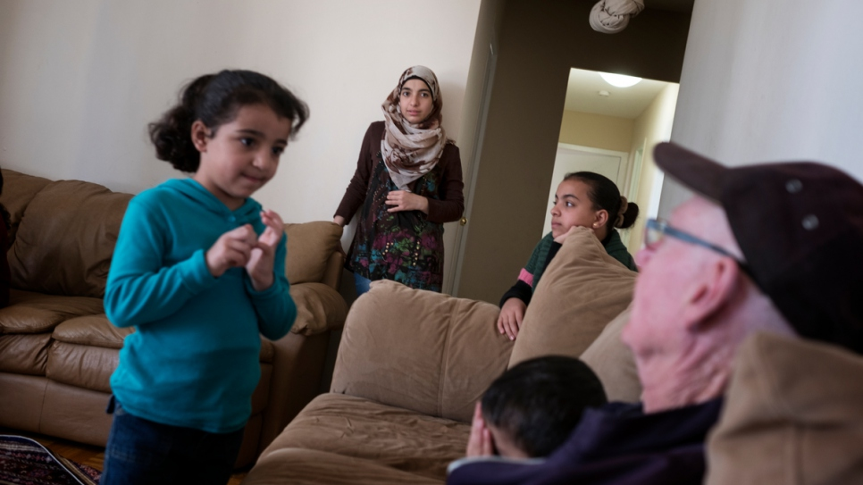 Sponsor Michael Adams (right) visits the Nouman family at their home in Toronto. The Nouman family is among the 13,000 refugees resettled in Canada over the past year.