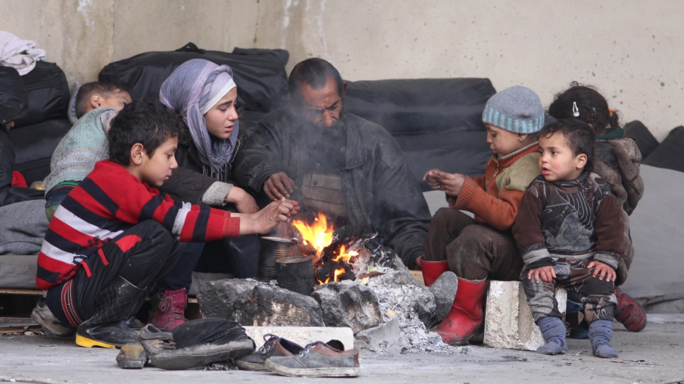 A displaced father and his children try to warm themselves around a fire at Jibreen Collective shelter in Aleppo.