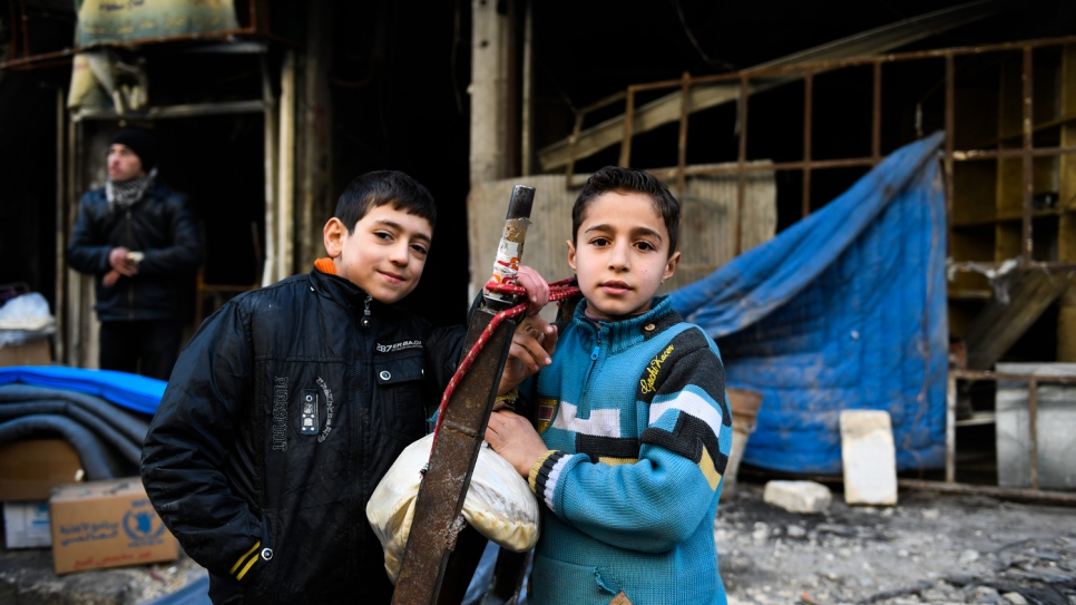 Children stand in front of a destroyed building in the Al-Mashatiyeh neighborhood of eastern Aleppo.