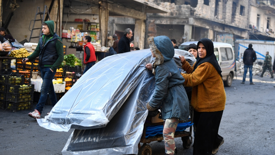 A woman and her two children push a cart carrying relief items distributed by UNHCR and other UN partners in the Tariq Al-Bab neighborhood in eastern Aleppo.