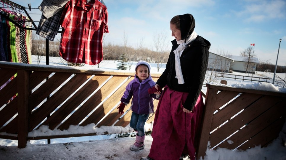Elaine Hofer takes Raghad Al Hamoud back into the house to warm up after tobogganing with other children at the Hutterite colony.