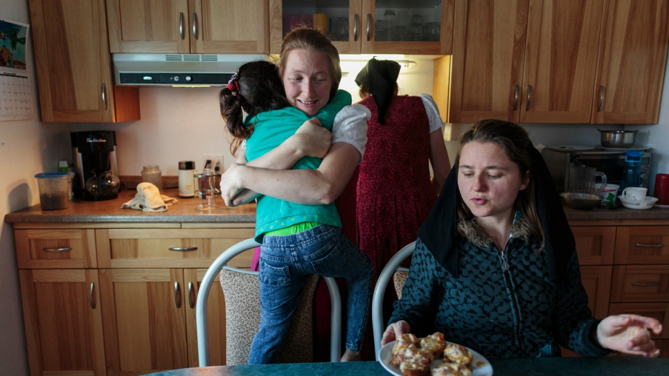 Elaine Hofer (left) hugs Raghad, the eldest Al Hamoud daughter, as Alice Hofer and Wanda Waldner prepare food for the young children.